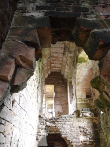 looking up at the second story hallway which would have lead from the great hall into private chambers. The charred walls are evidence of a large-scale fire that once consumed the castle.